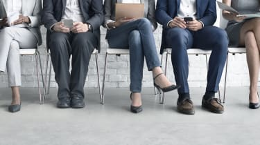 The legs of candidates waiting for a job interview
