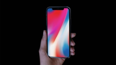 Apple iPhone X held in the hand with colourful wallpaper