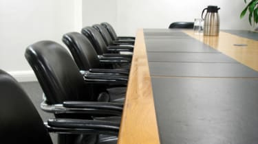 A corporate boardroom filled with empty chairs against a long table