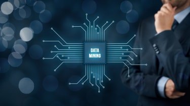 Graphic of data mining being shown on a virtual circuit board beside a businessman