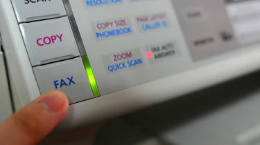 A person pushing the fax button on an old fax machine