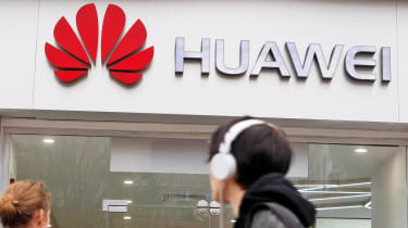 Huawei logo on the side of a building as people walk past