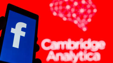 The Facebook logo on a phone in front of a large background with Cambridge Analytica