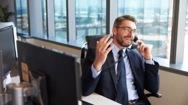 Man in a suit on the phone at his desk