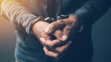 Closeup of a criminal's wrists in handcuffs