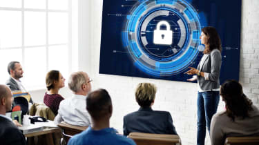 Business classroom with a woman talking about cyber security, blue padlock image on whiteboard