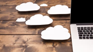 Pictures of white clouds on a desk besides a laptop