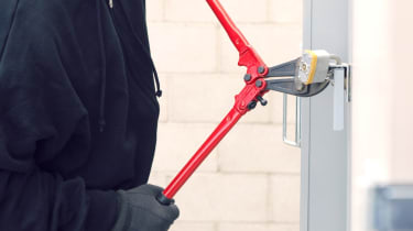A thief cutting a lock to break into a building