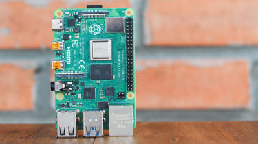 A Raspberry Pi 4 board in front of a red brick wall