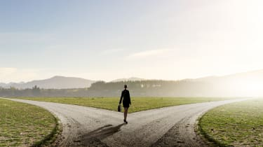 A business woman standing at a fork in the road, deciding which way to go