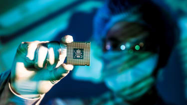A researcher holding up a new chip