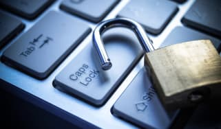Image of an unlocked padlock casually discarded onto on a keyboard