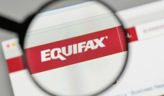 The Equifax logo being viewed under a magnifying glass