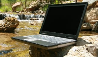 An old laptop turned off resting on a rock by a stream