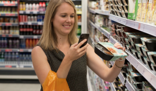 Woman using Sainsbury's SmartShop app to scan and pay for groceries