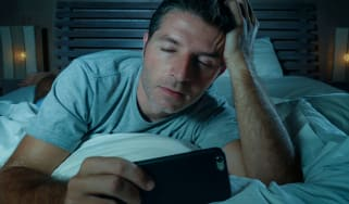 Tired man looking at his smartphone in bed