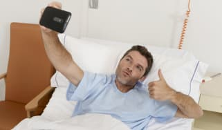 Man lying on hospital bed photographing himself in an amusing way