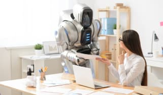 Representation of RPA showing an office worker and robot having a conversation by a desk