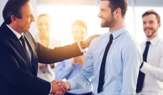 Photo of two men shaking hands in an office