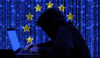 Hacker behind a computer against the EU flag to depict Brexit