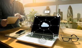 Laptop on a desk with a cloud illustration overlay, with icons to represent a virtual desktop