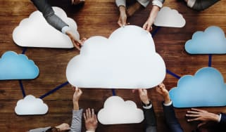 People sitting around a table, reaching in to hold a network of clouds