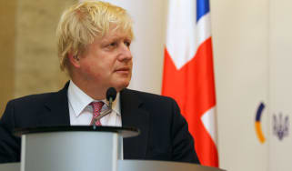 The UK prime minister Boris Johnson standing by a lecturn
