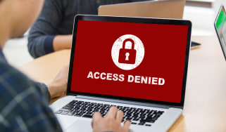 "A laptop screen showing ""access denied"" text on a red background"