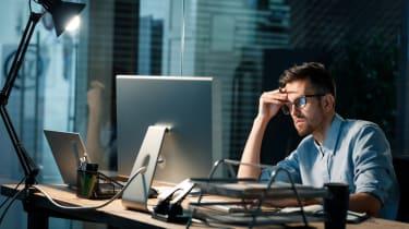 Stressed fella on a laptop in the dark