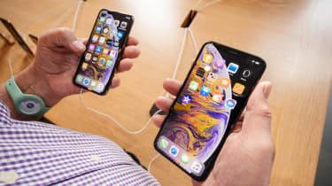 man looking at iPhones
