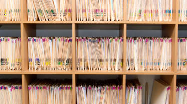 Stacks of paper patient records stored on a doctor's shelf