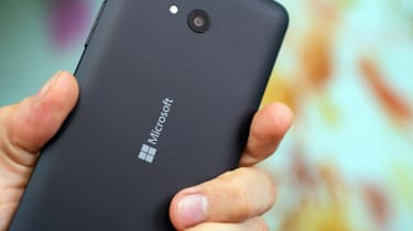 Windows 10 phone Lumia being held in the palm of a user's hand