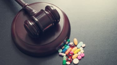 Gavel sitting beside a pool of prescription drugs