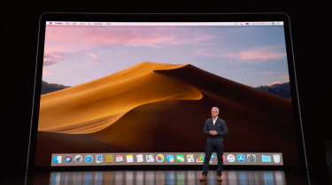 Apple CEO Tim Cook standing in front of a MacBook Air display at a special event in Brooklyn, New York