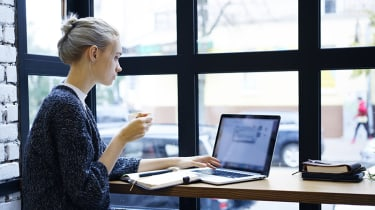 A woman remote working from a cafe using the cloud