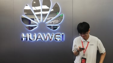 Man i front of Huawei sign