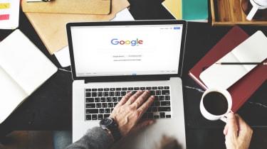 Man searching Google on laptop