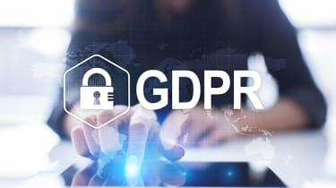 GDPR logo held above a person's fingers as they are processing data